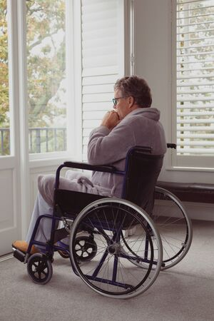 Side view of thoughtful disabled active senior Caucasian man looking through window on wheelchair in a comfortable home Stock Photo