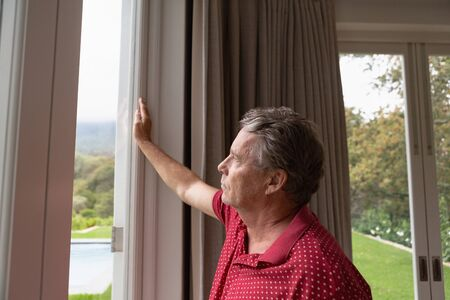 Side view of thoughtful active senior Caucasian man looking through window in a comfortable home