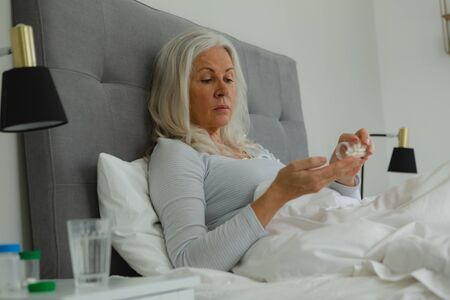Side view of active senior Caucasian woman taking medicine in bedroom at home
