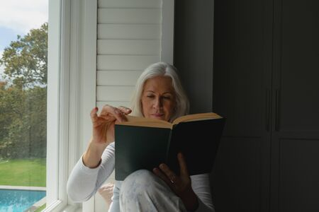 Front view of active senior Caucasian woman reading a book on window seat at home Stock Photo