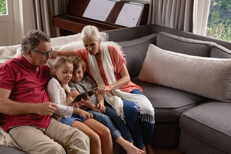 High angle view of multi-generation Caucasian family using digital tablet on sofa in a comfortable home Stock Photo