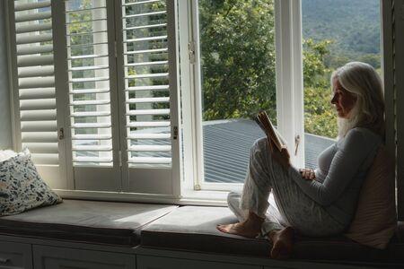 Widok z boku aktywnej starszej kobiety rasy kaukaskiej czytającej książkę na siedzeniu przy oknie w domu