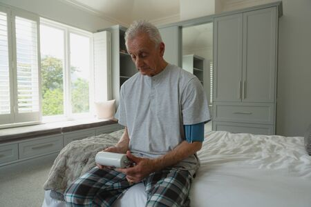 Front view of active senior Caucasian man measuring blood pressure with sphygmomanometer in bedroom at home