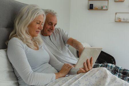 Seitenansicht eines aktiven kaukasischen Seniorenpaares mit digitalem Tablet im Schlafzimmer zu Hause bedroom
