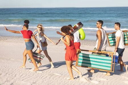 Side view of group of happy diverse friends walking together on the beach Standard-Bild