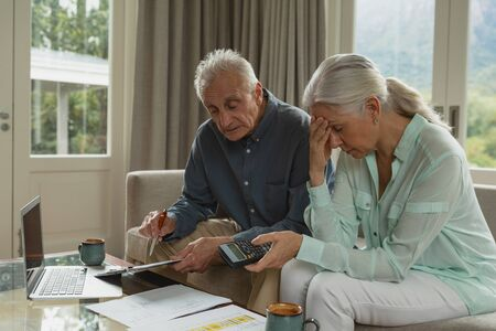 Side view of active senior Caucasian couple calculating bills in living room at home Stock Photo