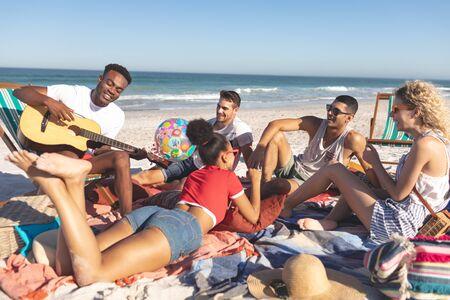 Widok z przodu grupy szczęśliwych różnorodnych przyjaciół bawiących się razem na plaży?