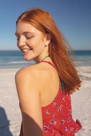 Side view of happy redhead Caucasian woman standing on the beach
