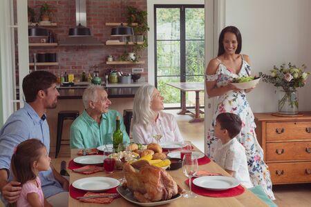 Vooraanzicht van een gelukkig Kaukasisch gezin van meerdere generaties dat thuis eten op de eettafel heeft