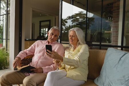 Front view of active senior Caucasian couple using mobile phone and reading a book in the porch at home Stock Photo