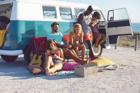Front view of group of diverse friends using mobile phone near camper van at beach Stock Photo