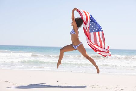 Side view of African american woman in bikini with american flag jumping on the beach Foto de archivo