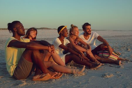 Side view of group of diverse friends sitting together on the beach during sunset