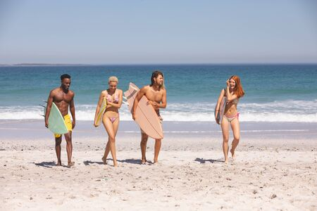 Front view of group of diverse friends walking with surfboard on the beach
