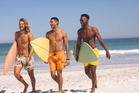 Vue de face d'amis masculins divers et heureux marchant avec une planche de surf sur la plage