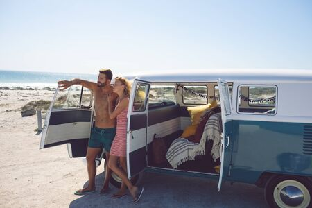 Front view of young Caucasian couple standing near camper van at beach in the sunshine Stock Photo