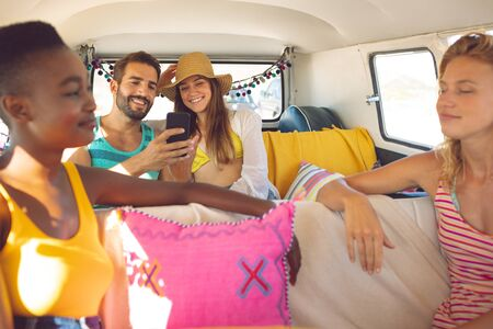 Front view of young group of diverse friends having fun in a camper van at beach