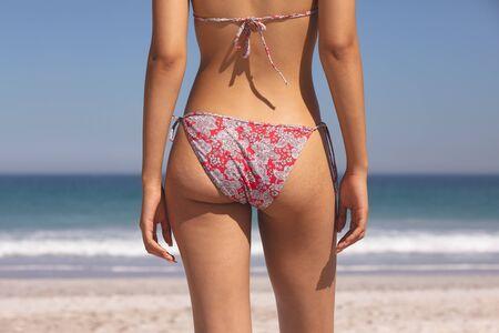 Medio sectie van gemengde rasvrouw in bikini die zich op het strand bevindt