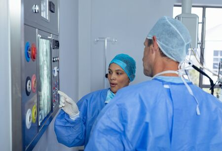 Side view of diverse surgeons discussing over x-ray report on x-ray light box in operating room at hospital