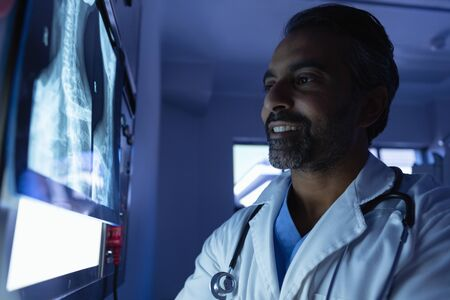 Side view of happy mature mixed race male doctor looking at x-ray on x-ray light box in operation room at hospital