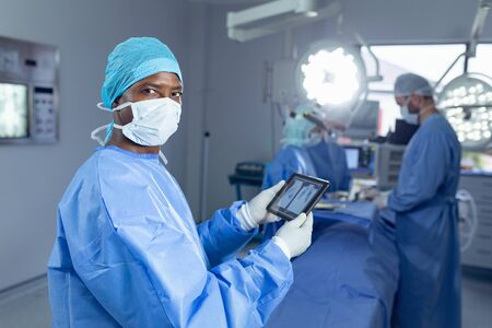 Portrait of African american male surgeon holding digital tablet while diverse surgeon working in operation theater at hospital Banque d'images