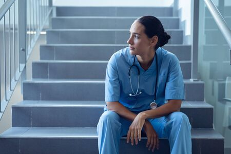 Vista frontal de la reflexiva doctora de raza mixta sentada en la escalera en el hospital