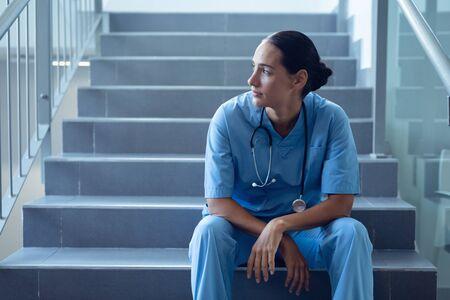 Vorderansicht einer nachdenklichen gemischten Ärztin, die auf der Treppe im Krankenhaus sitzt