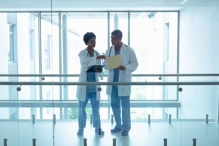 Front view of diverse male and female doctors interacting with each other in the corridor at hospital