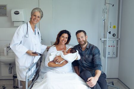 Front view of Caucasian couple with doctor holding their newborn baby in the ward at hospital