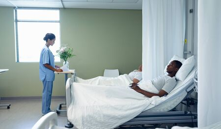Side view of mixed race female doctor looking at medical report while diverse men lying on bed in the ward at hospital
