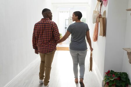 Rear view of couple walking hand in hand for shopping at home