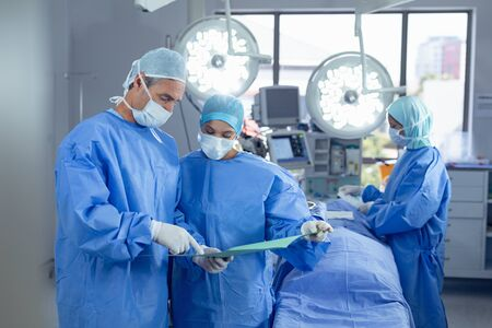 Front view of diverse surgeons discussing over medical file in operation room at hospital