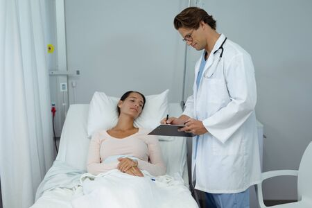Side view of Caucasian male doctor interacting with female patient in the ward at hospital.