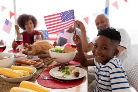 Side view of Multi-generation African American family celebrating US Independence day on a dining table at home Banco de Imagens