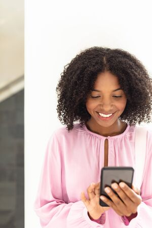 Front view of young pretty African-american employee looking her phone in modern office