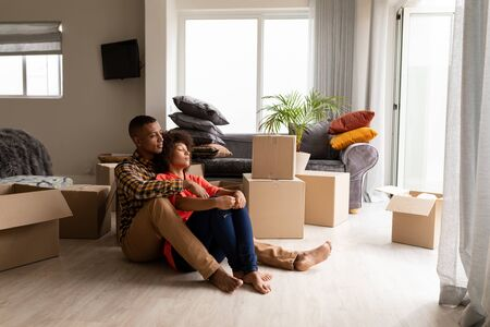 Front view of happy young mixed-race couple sitting together in living room at home. Couple is surrounded by cardboard boxes.