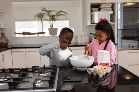 Front view of African american siblings preparing food on a dining table in kitchen at home