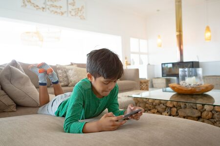 Front view of cute mixed-race boy playing game on mobile phone while lying on sofa at home.