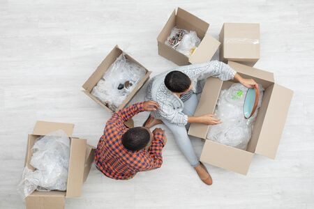 High angle view of happy African american couple unpacking cardboard boxes in living room at home