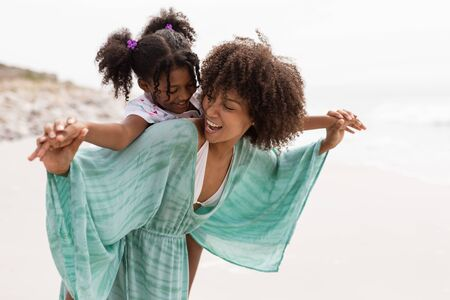 Front view of happy mixed-race mother giving piggyback ride to her cute young mixed-race daughter on the beach. 写真素材