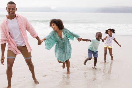 Vista lateral de la feliz familia afroamericana divirtiéndose en la playa