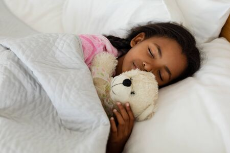 Portrait of African american Girl sleeping with teddy bear in bed in bedroom at home 免版税图像