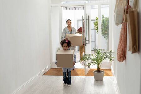 Front view of happy African american family with cardboard boxes entering their new home