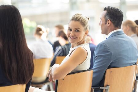 Side view of young Caucasian businesswoman sat in conference room, smiling to camera