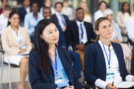 Vooraanzicht van diverse zakenmensen die op stoelen zitten terwijl ze luisteren naar spraak in de vergaderruimte Stockfoto