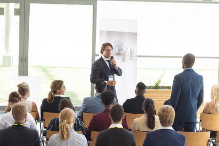 Vista posteriore del giovane dirigente maschio afroamericano che fa domande durante la conferenza