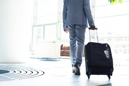 Rear view of young African-american male executive walking with suitcase