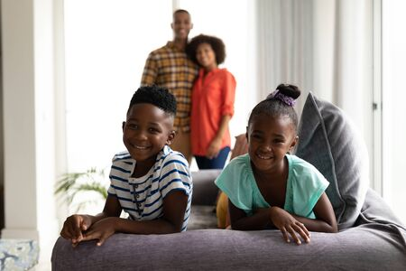 Front view of African american Children sitting on a sofa while their parents standing in the background at home