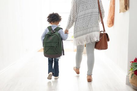 Rear view of African american girl with her mother walking together hand in hand near doorway at home