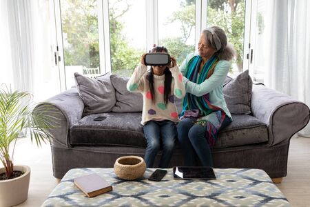 Front view of African american Grandmother helping his granddaughter to wear virtual reality headset in living room at home